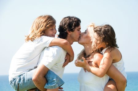 Couple in love kissing each other as kids enjoy the piggy ride Stock Photo - 5746085