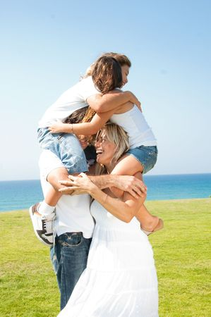 Cute young kids embracing each other as they sit up on the shoulders of parents