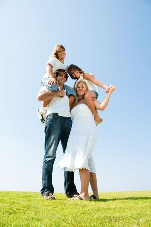 Parents with kids on their shoulders smiling Standard-Bild