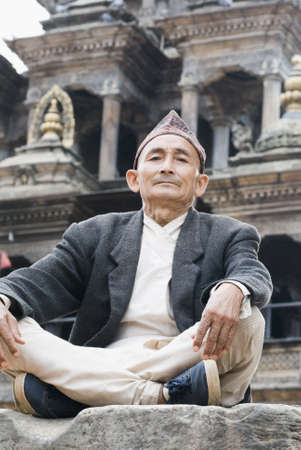 Low angle view of a senior man sitting cross-legged on a rock photo