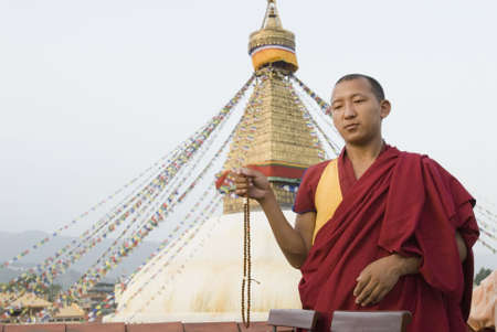Low angle view of a monk holding prayer beads in front of a temple