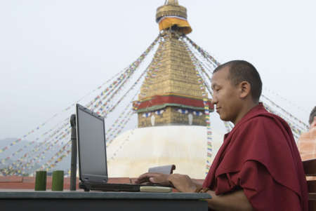 Side profile of a monk using a laptop Stock Photo - 653164