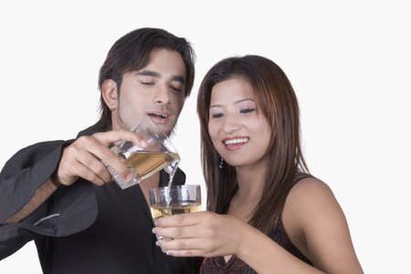 Close-up of a young man pouring white wine into a young woman's wine glass photo
