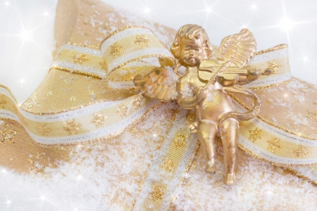 Close up of golden present box with angel playing violin photo