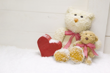 Two teddy-bear sitting with red wooden heart photo