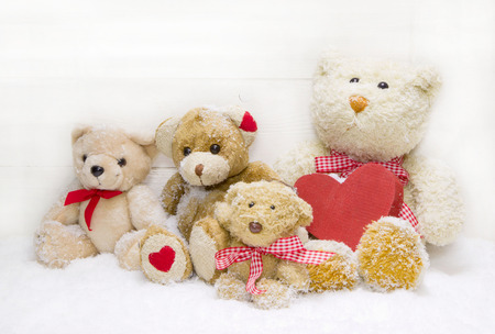 Group of teddy-bear sitting with red wooden heart photo