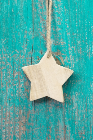 Hanging wooden star decoration on wooden background photo