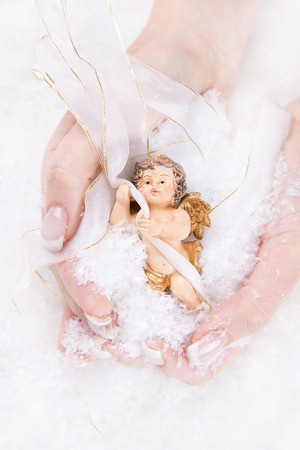 angel figurine: Local Caption     Woman holding china angel in her palm Stock Photo