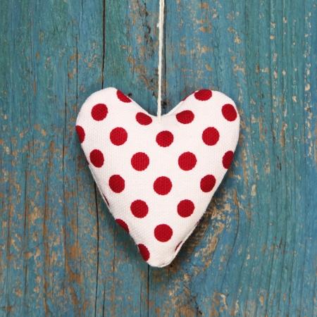 polka dotted: Polka coraz�n punteado en la superficie de madera de color turquesa