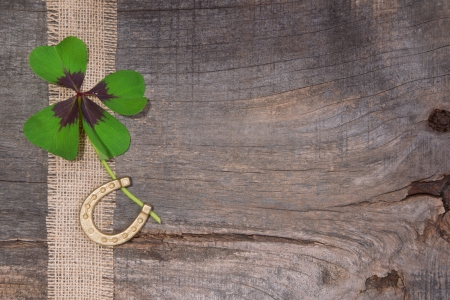 fourleaf: Horseshoe and four-leaf clover on wooden surface