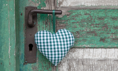 shabby chic: Checkered green textile heart hanging on door handle Stock Photo