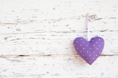 purple heart: Romantic heart shape hanging above white wooden surface  Stock Photo