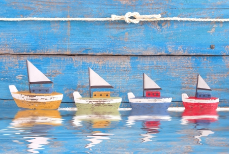 Shabby toy boats in a row on a wooden blue background - concept for cruising, sailing, holiday photo