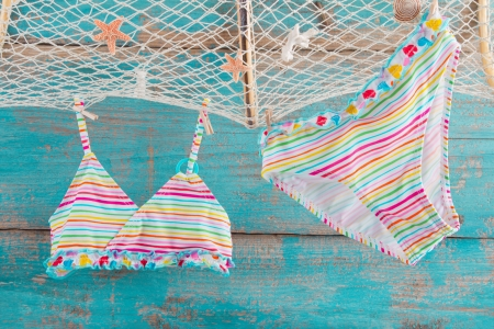 Bikini - concept for holiday, summer, beach on a wooden turquoise background