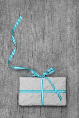 giftbox: Giftbox with turquoise striped ribbon for anniversary or christmas on a wooden background