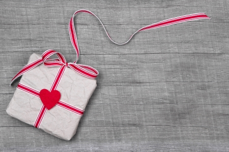 White Christmas or birthday gift box with red ribbon and a red heart on grey wooden background Stock Photo - 22780253
