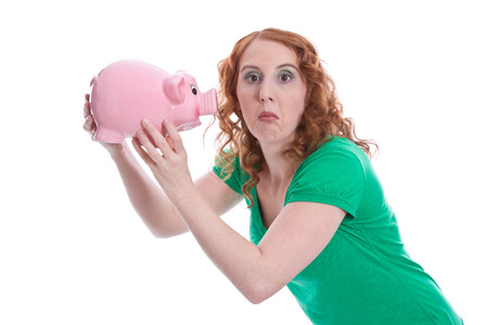 disappoint: Portrait of a redhead woman shaking a piggy bank against white background Stock Photo