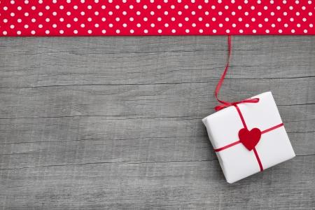 Geschenk of aanwezig met rode harten voor moeder s, Valentijnsdag, Kerstmis of verjaardag op een houten achtergrond voor een wenskaart