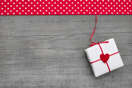 Gift or present with red hearts for mother s day, valentine s day, christmas or birthday on a wooden background for a greeting card photo
