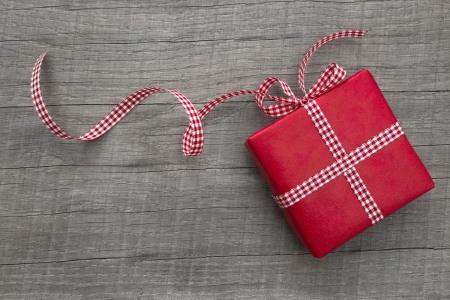 One red present with a checkered ribbon for christmas, birthday, valentine, wedding or mothers day photo