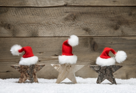 e card: Three wooden stars for christmas on a wooden background with snow