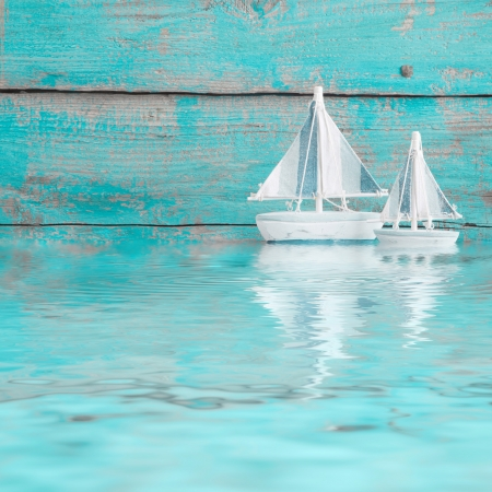 Toy sailboats on the water as a wooden background in turquoise photo