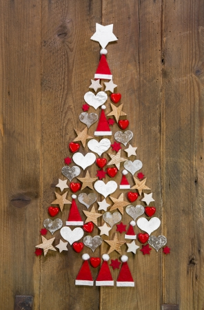 Christmas tree in red and white colour on a wooden background - decoration idea for advent Фото со стока