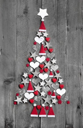 Christmas tree made up of decoration on grey wooden background photo