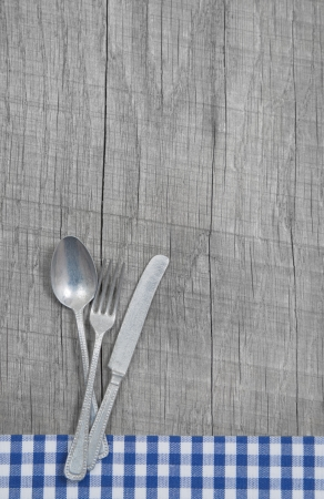 Spoon, fork and knife on wooden shabby country style background with a blue bavarian checked frame photo