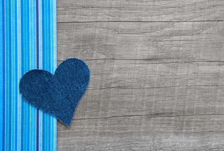 Denim blue heart on wooden background in country style photo