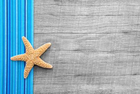 Starfish on wooden background with a blue striped frame in shabby style photo