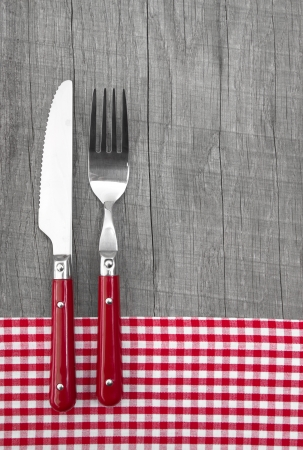 menue: Fork and knife with red checkered frame on a wooden background