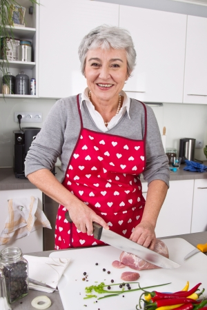 golden ager: Senior or older woman with grey hair cooking in kitchen