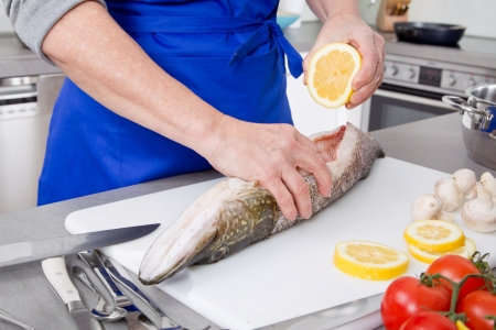 Cooking fish with citrone at home - woman is preparing dinner for sunday