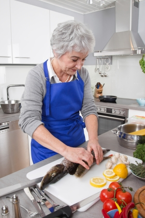 golden ager: Woman is preparing dinner - with fish in the kitchen