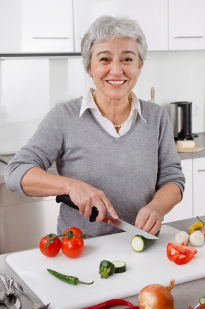 golden ager: Best age senior woman in the kitchen with gray hair Stock Photo