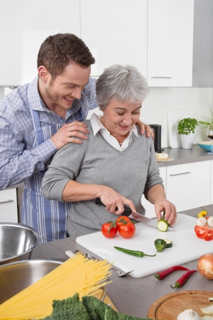 golden ager: Son with his mother cooking together and cut vegetables Stock Photo