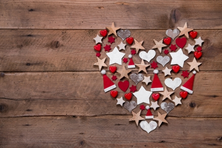 Christmas heart on a wooden background with different decoration in red and white photo