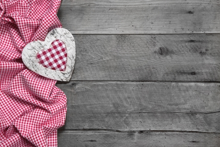 Wooden background for a greeting card or a voucher with a red chequered heart for christmas photo