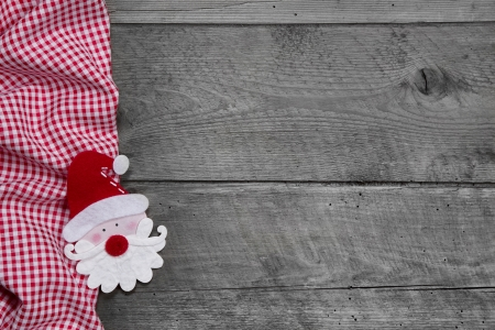 Red and white checkered fabric with santa head on grey wooden background for christmas photo