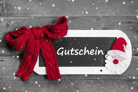 compliments: Red bow on chalk board with Voucher - Gutschein message on snowflake designgrey wooden background - for christmas Stock Photo