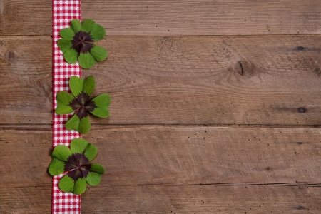 Wooden background with red and white checkered ribbon and green clovers photo