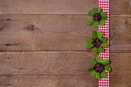 Wooden background with red and white checkered ribbon and green clovers for a happy new year photo