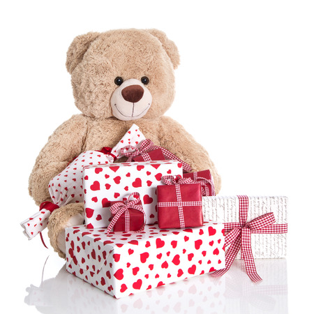 Christmas  Teddy bear with pile of red and white birthday or valentines presents on white background  photo