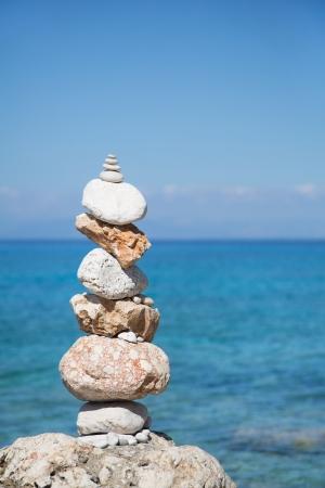 paz interior: Mar de fondo azul con un pilar de piedras para los conceptos meditativas o espirituales Foto de archivo