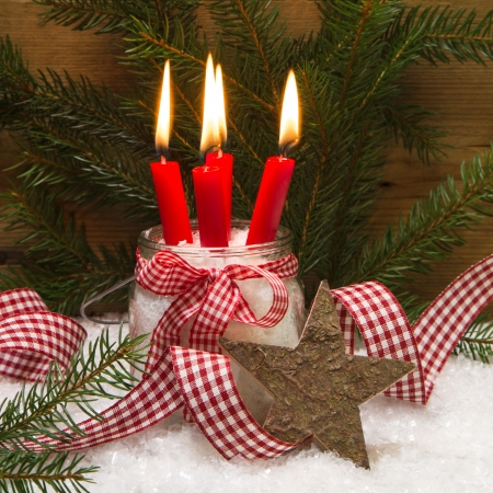 Square Christmas card decorated with four red burning candles, wooden star, snow, ribbon and pine branch photo