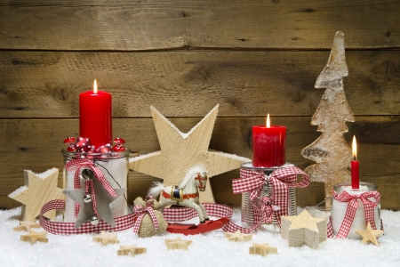 Decorated Christmas card with red candles and stars on wooden background photo
