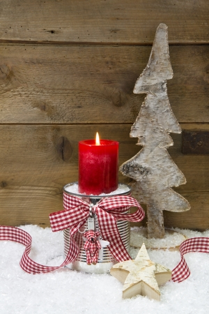 Christmas decoration wooden tree,stars,candle and snow on wooden background with copy space for a greeting card photo