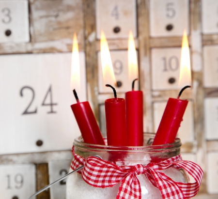 advent candles: Christmas eve  four red burning candles with a shabby white advent calendar background