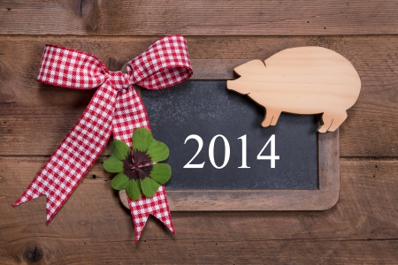 Happy new year 2014 - greeting card on a wooden background with a lucky pig and a green clover with a red checked ribbon  photo